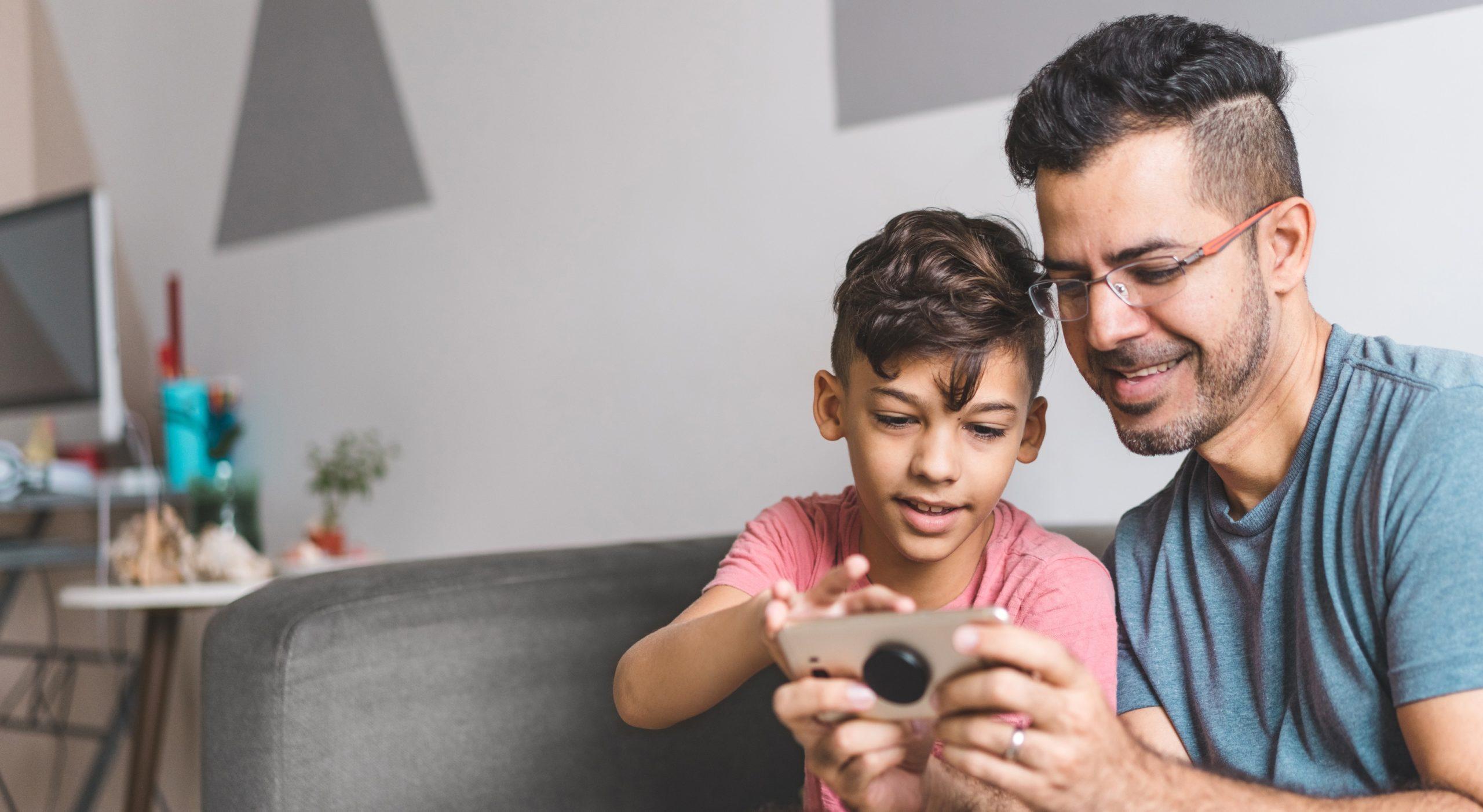 Padre e hijo mirando el celular