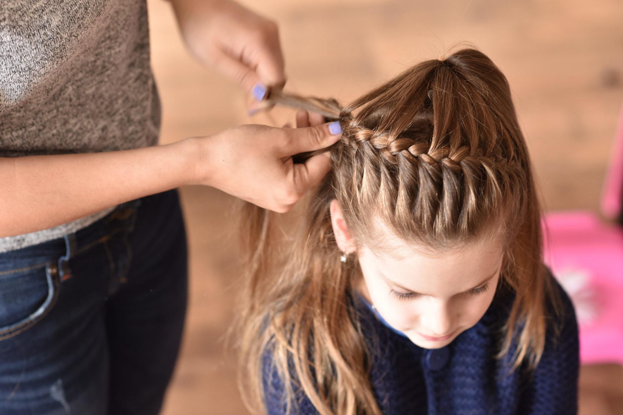 mujer trenzando el cabello de una niña